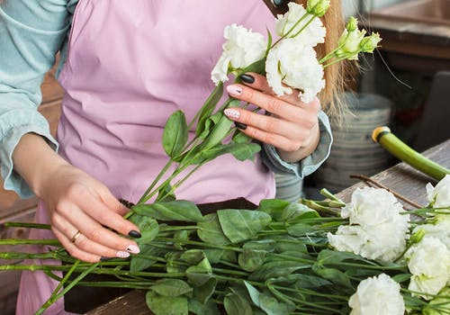 A woman handles the leaves of an average-sized floral bouquet