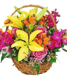 Bright yellow, orange and pink flowers in a basket with butterfly decorations.