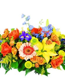 Bright yellow, orange and purple flowers with greenery arranged in a centerpiece.
