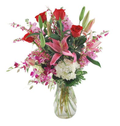 Hydrangea, red roses, stargazer lilies, stock and orchids in a clear glass vase.