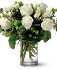 White roses and green berries in a glass cylinder vase.