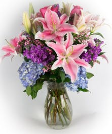 Stargazer lilies, roses, hydrangea and stock in a clear glass vase.