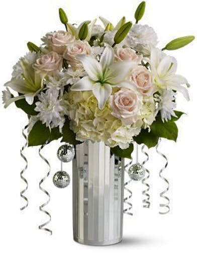 White and creme flowers set off by tiny disco balls and silver ribbon in a silver vase