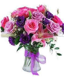 Pink, lavender and purple flowers in a glass vase tied with purple ribbon.
