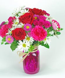 Hot pink carnations, red roses and white daisies in a pink mason jar.