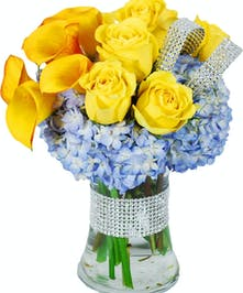 Sunset callas, yellow roses and blue hydrangea in a clear glass vase with a touch of bling.
