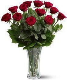 A dozen long stem red roses arranged in a clear vase with elegant greenery.