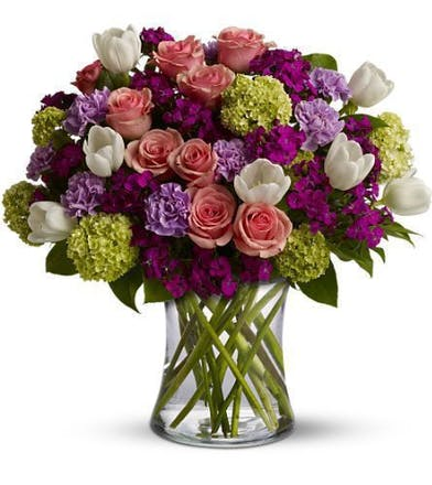 Roses, tulips and carnations in huse of pink, purple, white and green in a clear glass vase.
