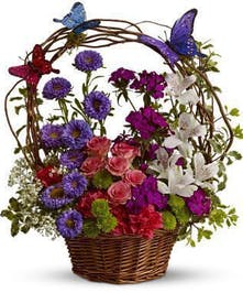 Basket of flowers accented with butterfly decorations.