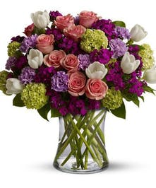 Pink, purple, green and white flowers in a clear glass vase.
