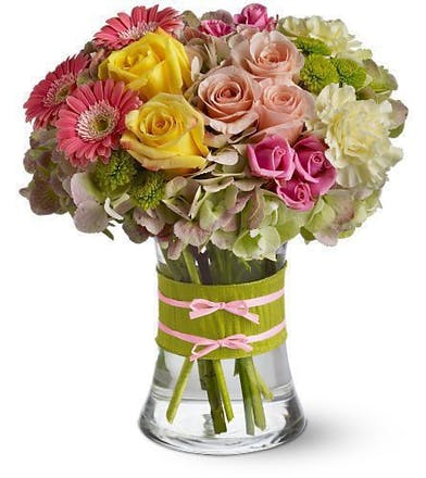 Pink, yellow and green roses, gerbera daisies and hydrangea in a clear glass vase with pink ribbon tied around.