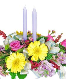 Bright floral centerpiece with two lavender candles in the center.