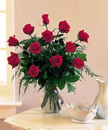 One dozen red roses with baby's breath in a glass vase.
