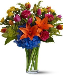 Bright orange, blue and pink flowers in a clear glass vase.