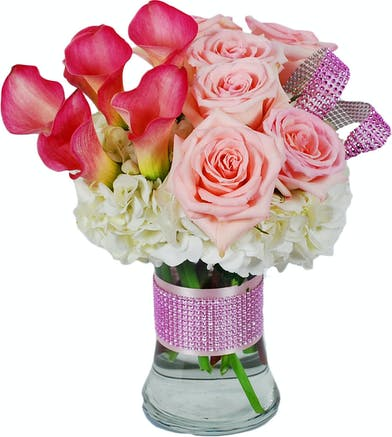 Light pink and hot pink flowers in a glass vase accented by pink bling.
