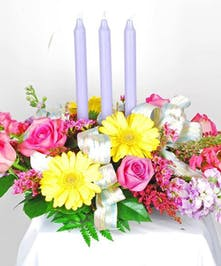 Floral centerpiece made with yellow, pink and white flowers with three lavender candles in the center.