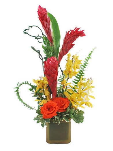 Tropical and exotic flowers in oranges and yellows in a green cube vase.