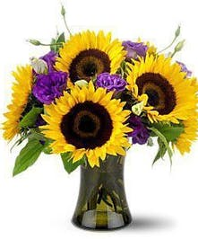 Sunflowers and lisianthus in a clear glass vase.
