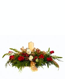 Christmas centerpiece of greenery, red flowers, berries, pine cones and a pillar candle.