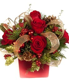 Red vase of red roses, greenery, pine cones, ribbon and ornament accents.