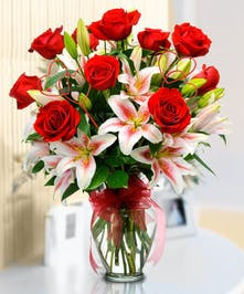 Stargazer lilies and red roses in a clear glass vase.