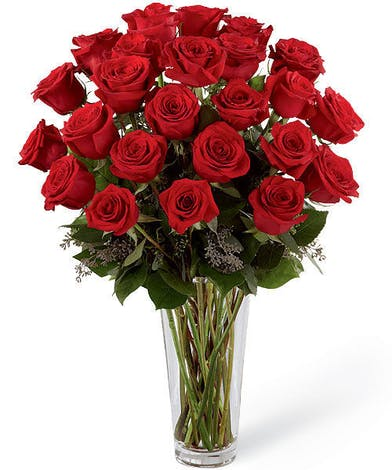 Two dozen (24) red roses and greenery arranged in a clear glass vase.