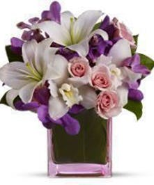 Roses, orchids and Asiatic lilies in shades of white, pale pink and purple in a pink cube vase.