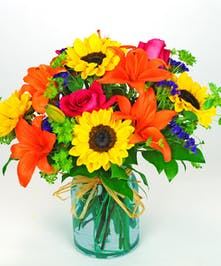Vibrant orange asiatic lily, hot pink roses, and sunflowers accented with bupleurum in a green glass vase.