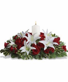 A dozen red roses, white Asiatic lilies and fresh evergreens are arranged in a dish around a white pillar candle