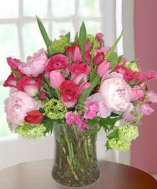 Hot pink peonies, roses, ranunculus, tulips, sweet peas and viburnum in a clear glass vase with curly willow.