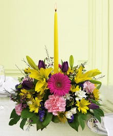 Bright floral centerpiece with a single yellow taper candle in the center.