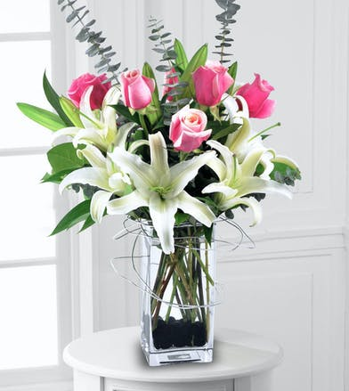 White lilies, pink roses and eucalyptus in a clear rectangular vase with marble-lined bottom.
