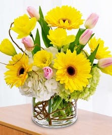 White hydrangea, yellow gerbera daisies, yellow daffodils and pink tulips in a clear glass vase.
