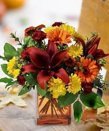 Red, yellow and orange flowers in a wicker basket.