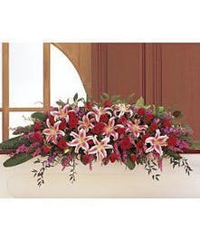 Casket spray of stargazer lilies, red roses, heather and more.