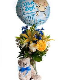 Vase of assorted flowers with a plush teddy bear and mylar balloon that says