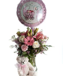 Pink and white flower arrangement in a clear glass vase accompanied by a stuffed bear and mylar balloon that says