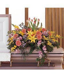 Casket spray of yellow lilies, pink gerbera daisies and tulips, and more with greenery.