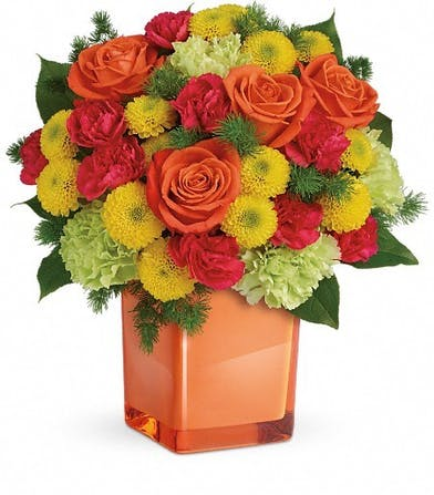 Roses, carnations and mums in an orange cube vase.