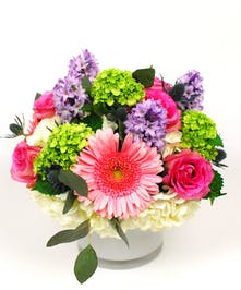 Hyacinths, gerbera daisies, and hydrangeas in a clear glass vase.