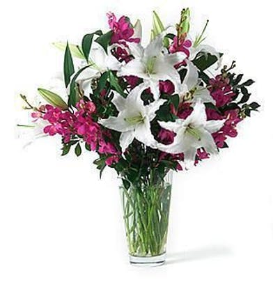 Orchids and Casablanca lilies in a clear glass vase.