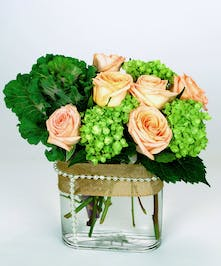 Green and peach flowers in a glass cube vase accented with pearls.