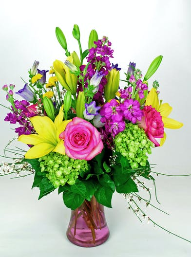 Stock, lily, roses, and hydrangea in a clear pink glass vase.