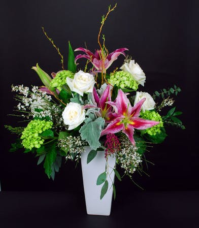 Roses, hydrangea, dusty miller and Oriental lilies in a tall ceramic vase.