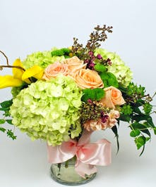 Lime green hydrangea, yellow callas, peach roses and purple was flower in a clear glass vase tied with a bow.