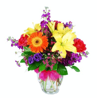 Multicolored roses, lilies, lisianthus and gerbera daisies in a glass vase accented with a hot pink bow