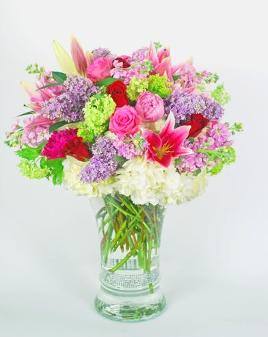 Glass vase filled with bright pink, purple, green and white flowers.