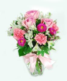 Pink & white roses, carnations and alstomeria in a clear glass vase with pink ribbon bow.