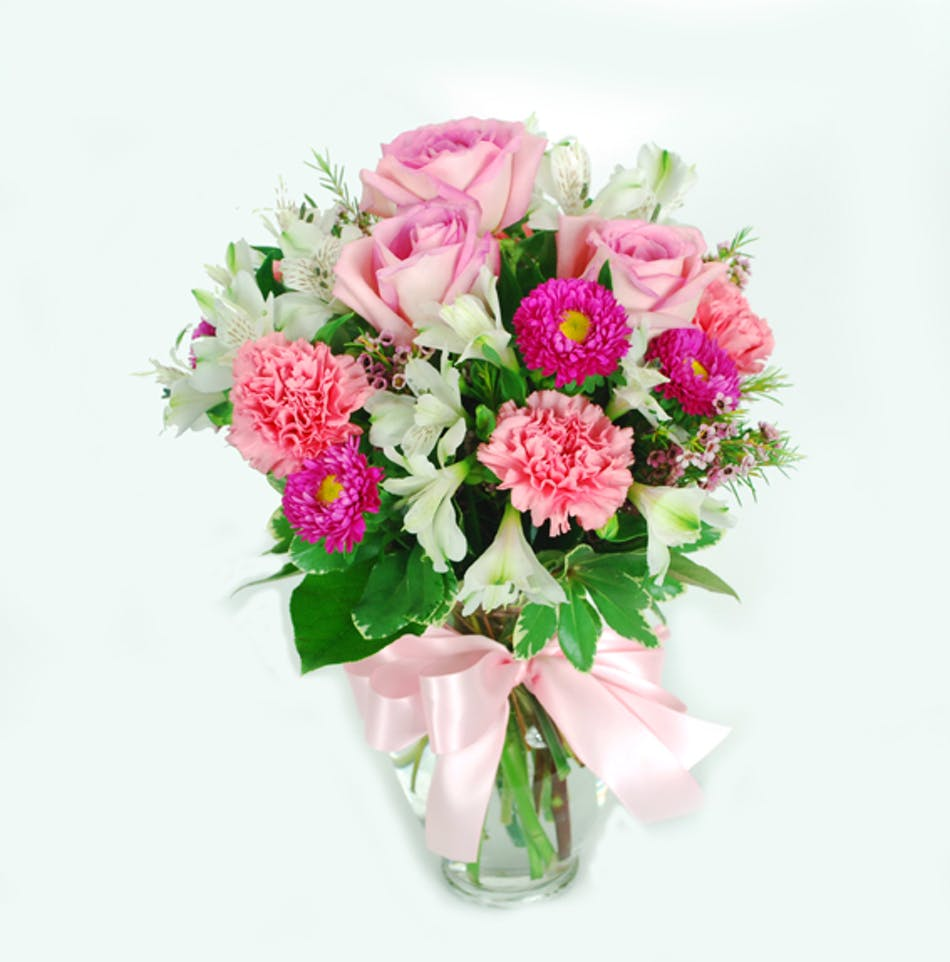 A mix of fresh s such as roses, carnations and alstomeria – in shades of pink, white – is delivered in a vase adorned with a matching ribbon. - Apx 11