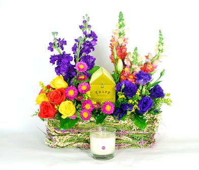Bright purple, yellow and pink flowes surrounding a Trapp candle inside a basket.